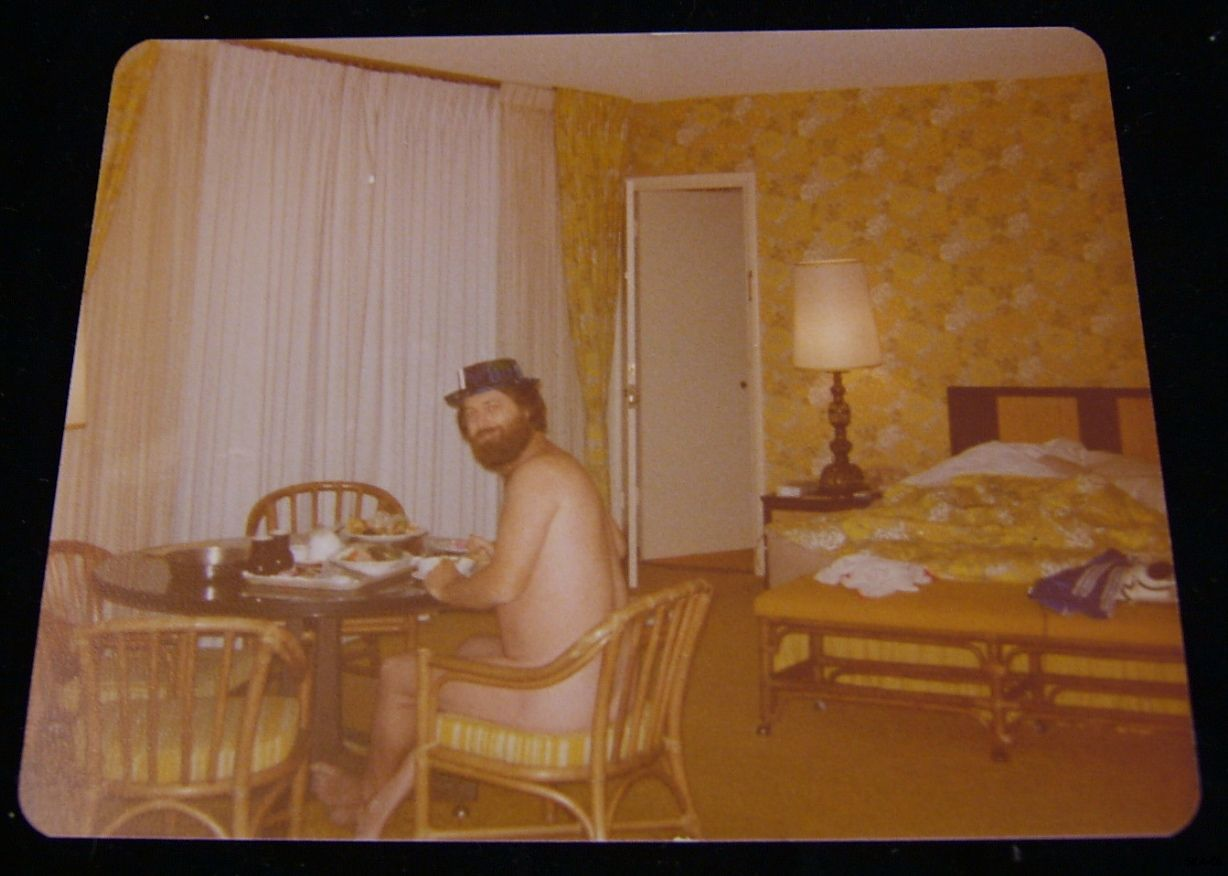 A picture of Brian Wilson, sitting at a table, nude, some time between 1977 and 1981-ish